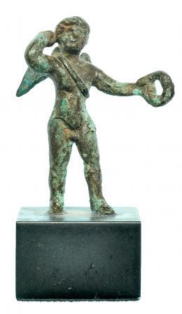 719  -  ROMA. Imperio Romano. Bronce. Figura exenta de Cupido con carcaj y corona de laurel. Alura: 5,1 cm. Incluye peana. Procedente de colección privada española años 2000.