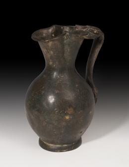 1111  -  PERÍODO RENACENTISTA. Jarra (XVI d.C.). Bronce. Con asa floral con apéndice distal con cara de sátiro. Altura 21,6 cm.
